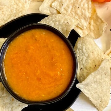 mango habanero salsa in a black bowl surrounded my tortilla chips