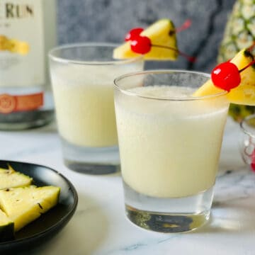 frozen pina colada in a small glass with cherries and pineapple garnish