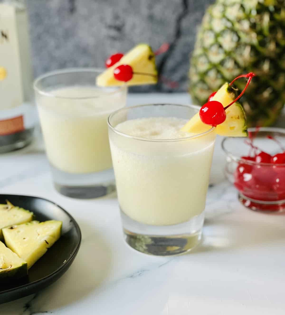 frozen pina coladas on a gray background in small tumbler glasses