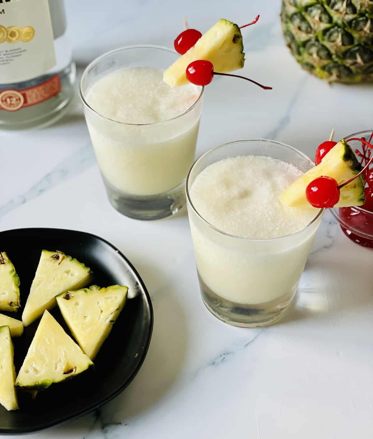 frozen pińa coladas with pineapple and cherries on a white background