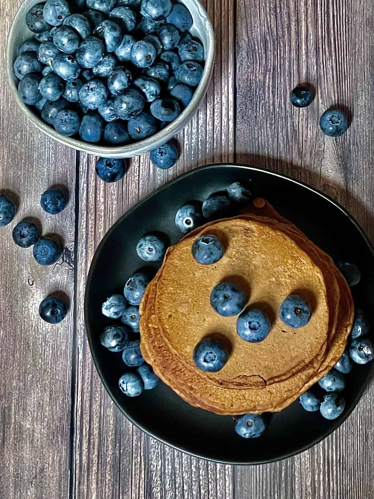 chocolate chip pancakes topped with blueberries overhead shot
