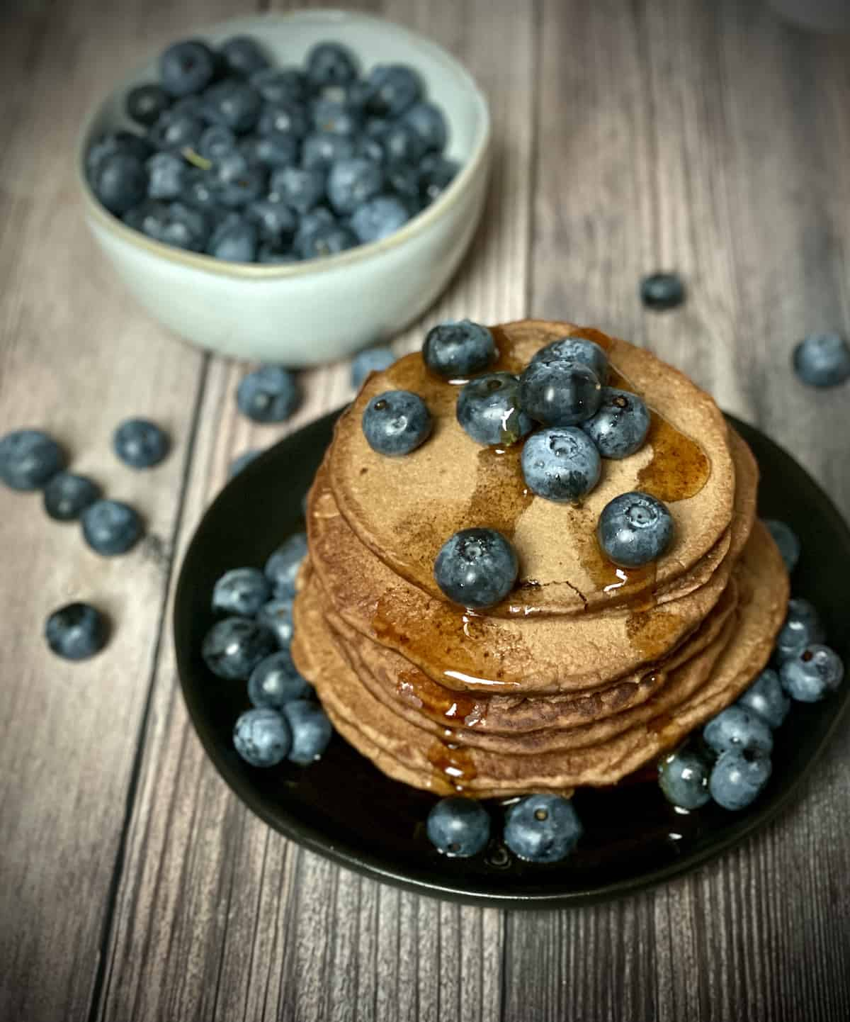 pancakes with blueberries and maple syrup in a stack