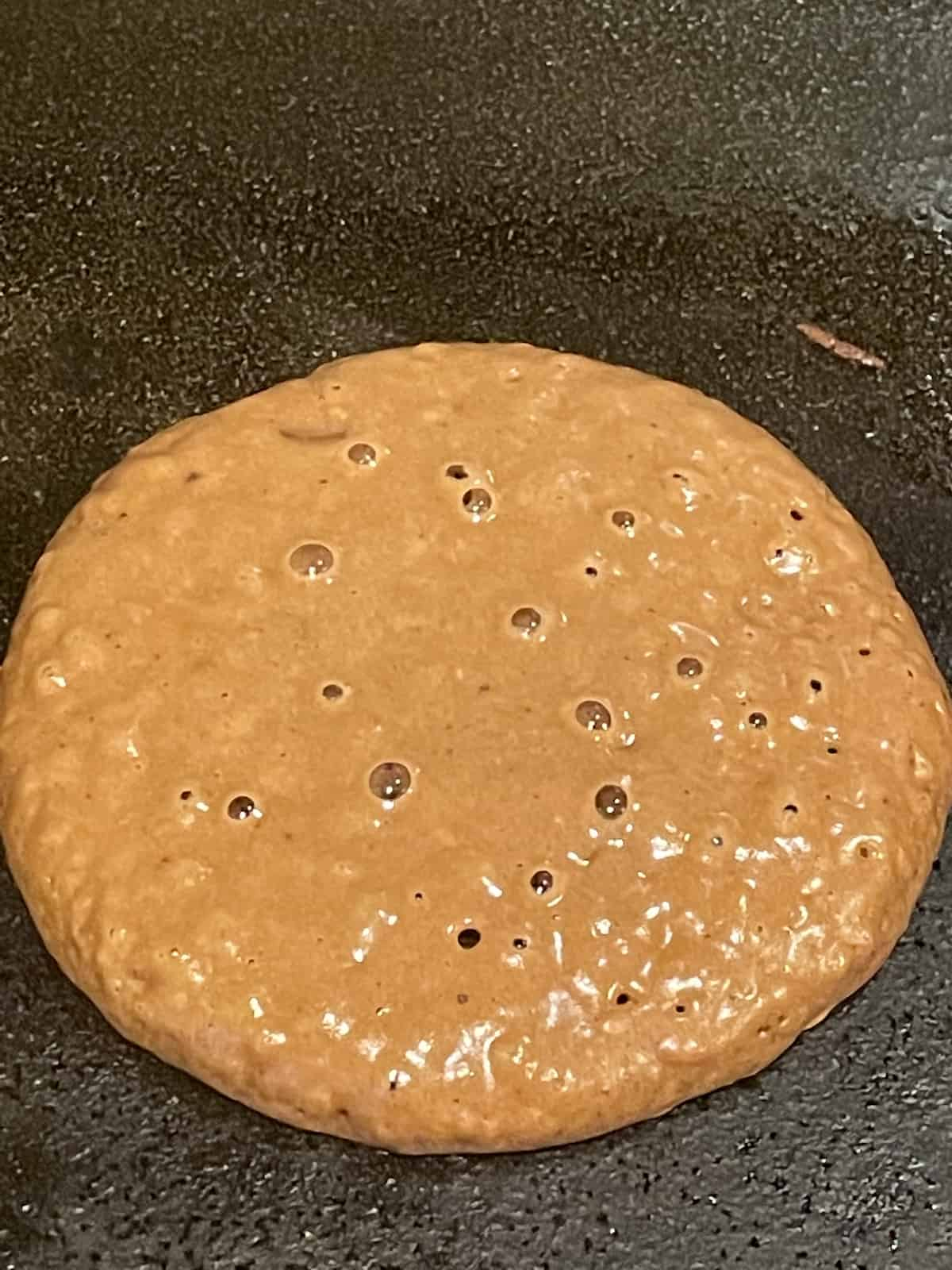chocolate pancake on a griddle before being flipped