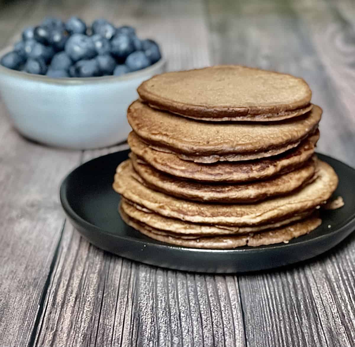 a stack of chocolate chip pancakes on a black plate