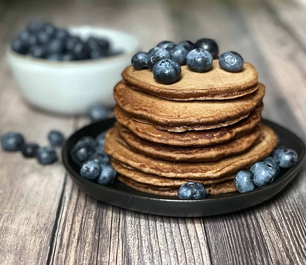 stack of pancakes topped with blueberries