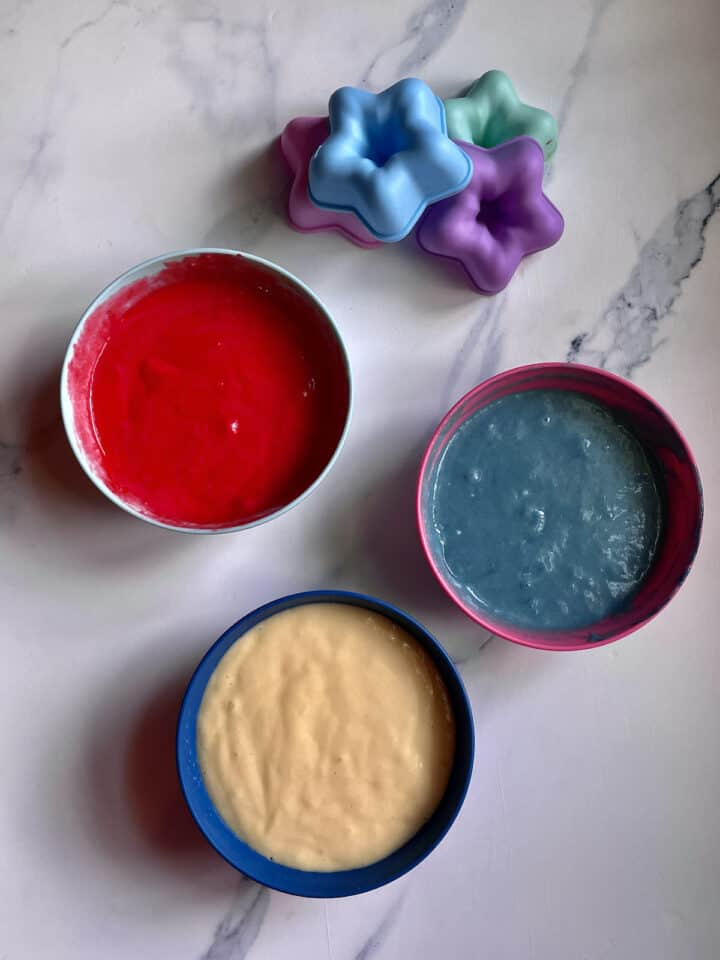red white and blue cake batter in separate bowls