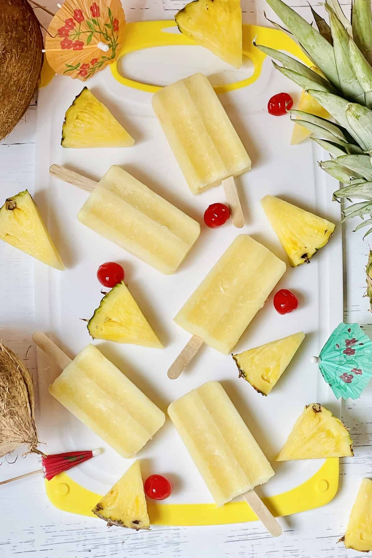 pina colada popsicles on a cutting board surrounded by cherries and pineapple slices
