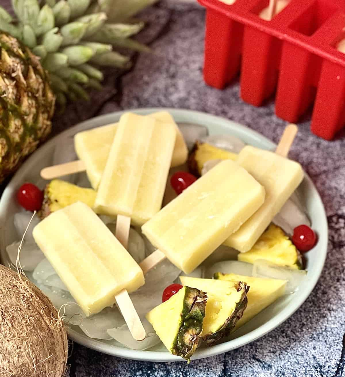 pina colada popsicles in a stack on a plate