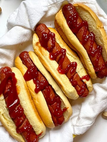 air fryer hot dogs in buns with ketchup in a basket