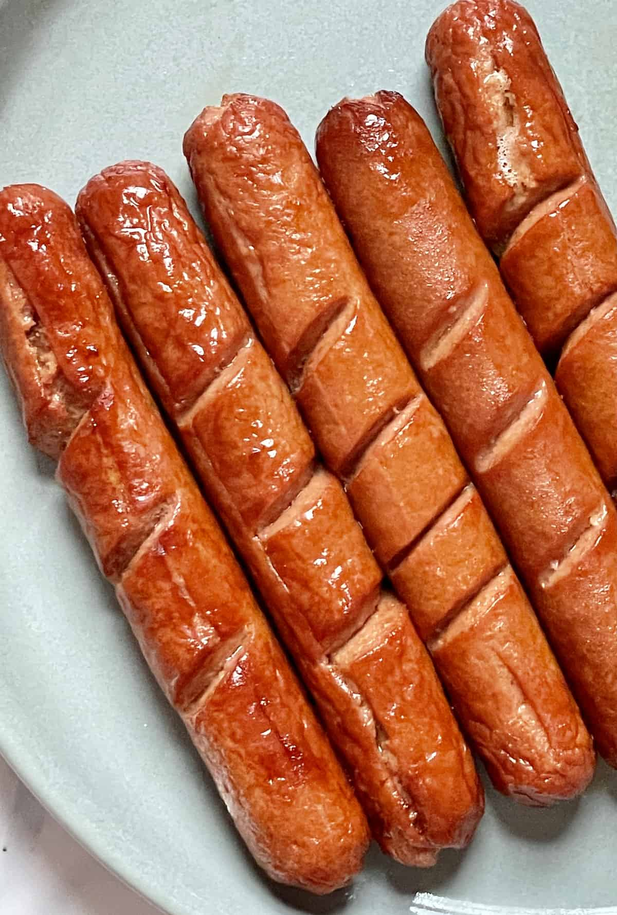 hot dogs with slits on a gray plate