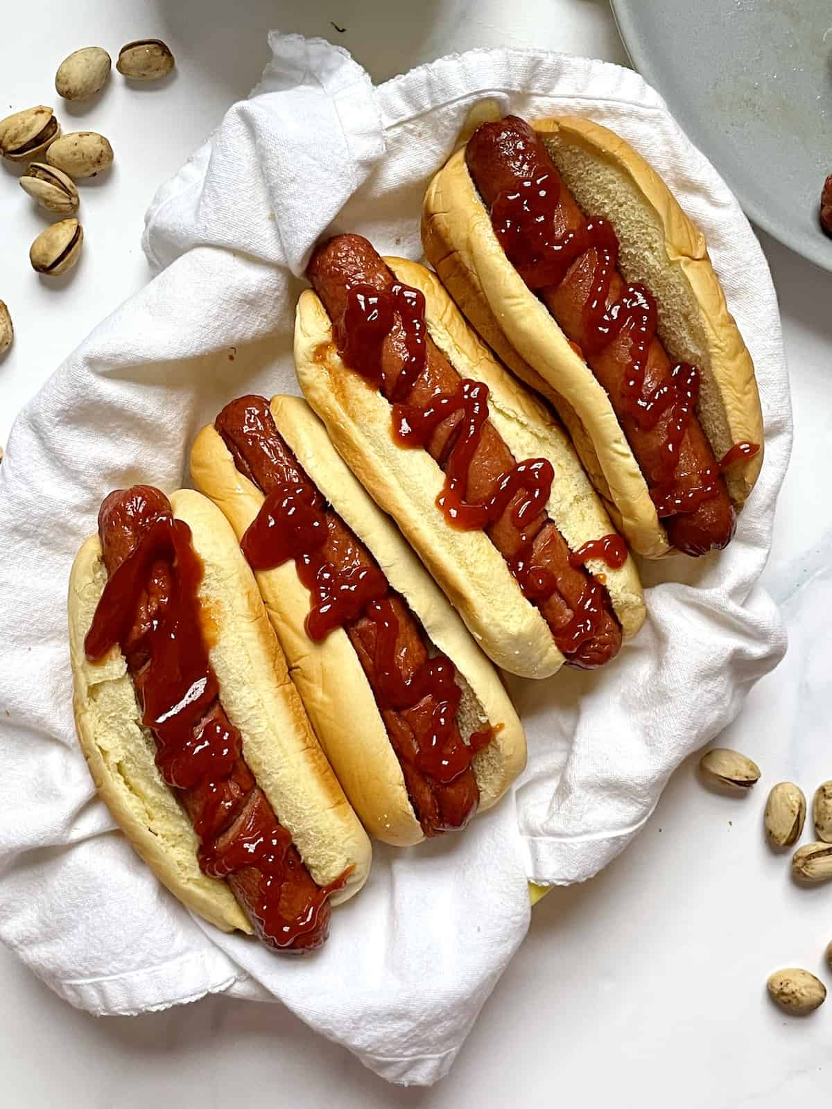 air fryer hots in a basket with ketchup and pistachios
