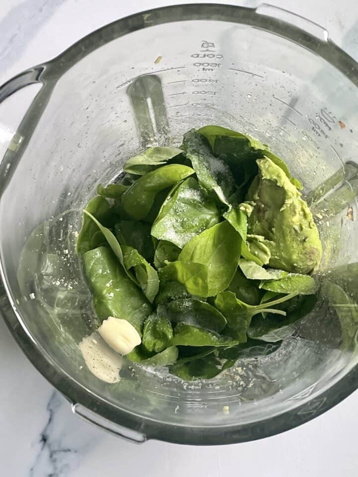 basil, spinach, avocado, garlic and pine nuts in a blender