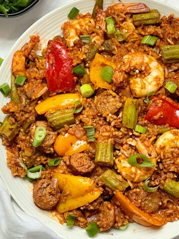 instant pot jambalaya with shrimp and sausage on a white plate topped with scallions