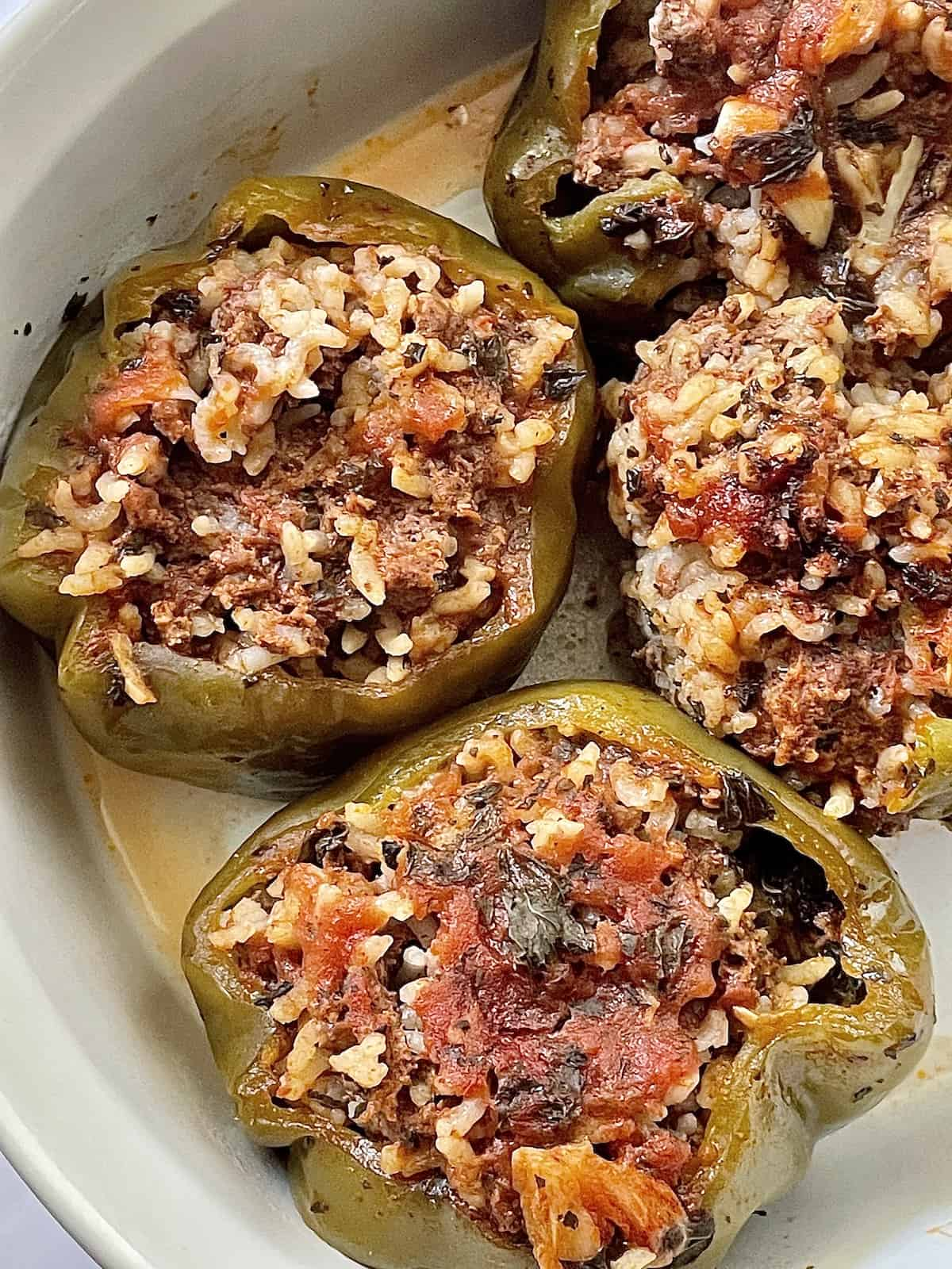 Stuffed bell peppers in a white casserole dish