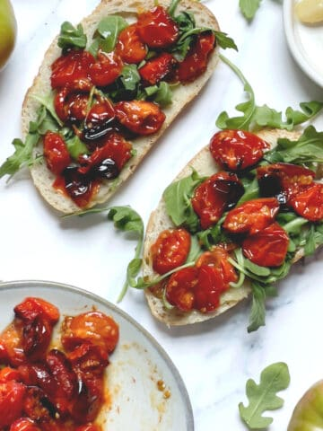 air fried cherry tomatoes on a piece of bread with arugula