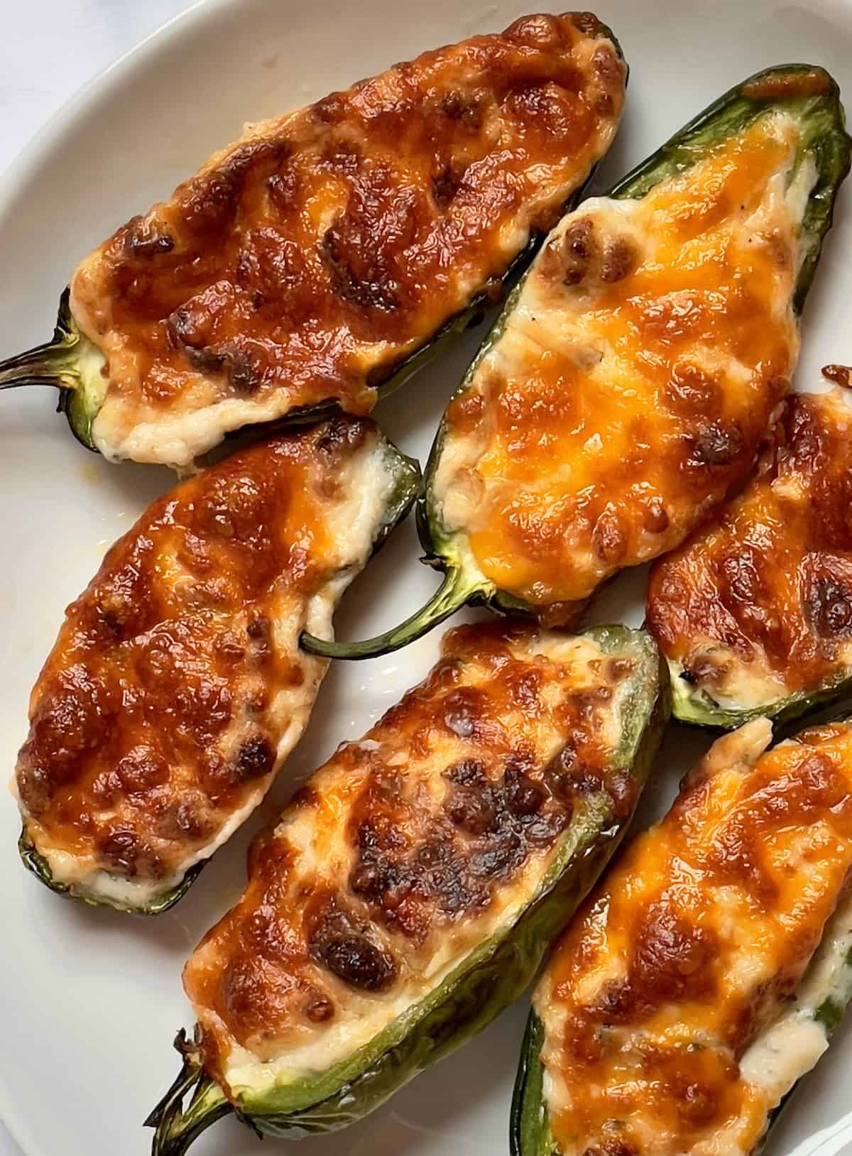 air fried cheesy jalapeno poppers on a white plate