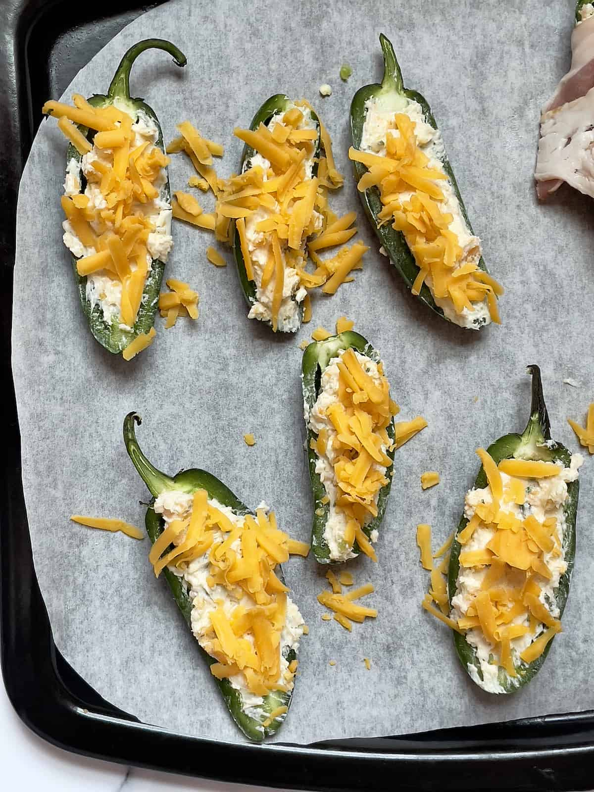 jalapeno poppers topped with shredded cheddar cheese on a baking pan
