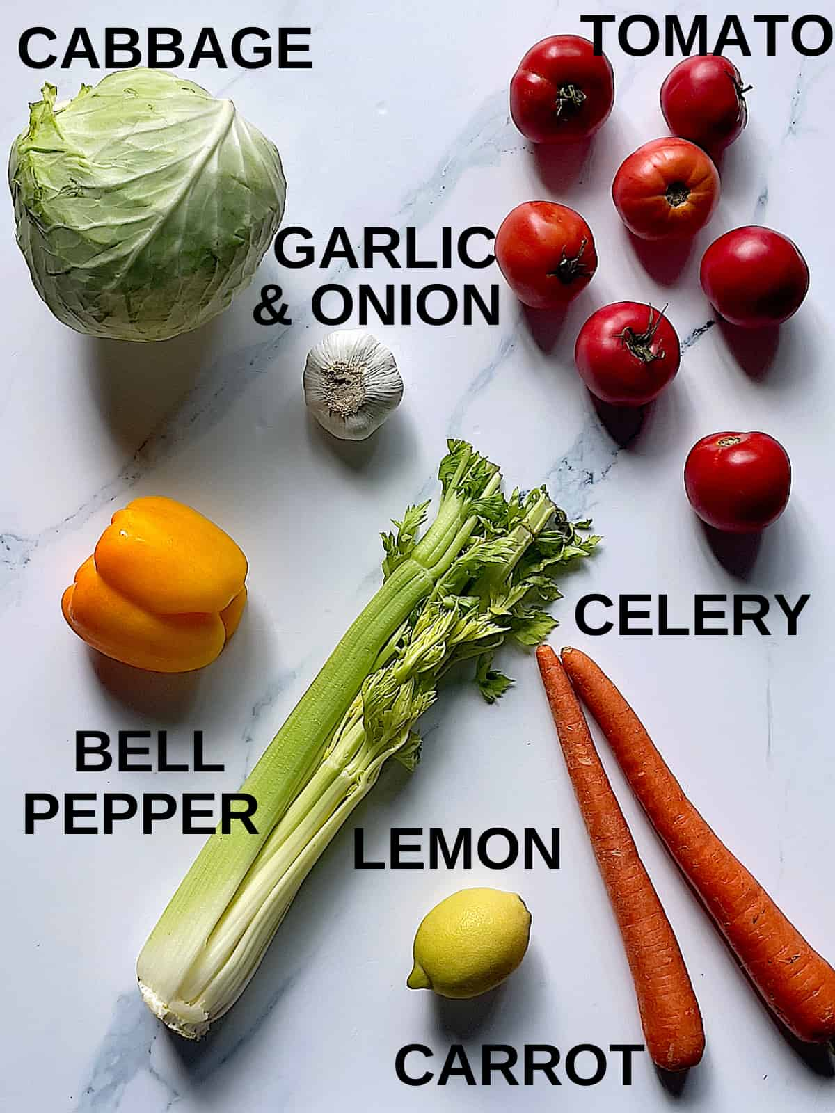 tomato, cabbage, bell pepper, garlic, celery, carrots, and lemon on a white background