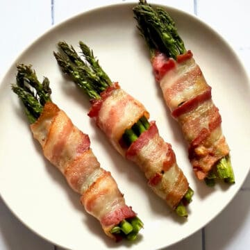 air fried bacon wrapped asparagus on a white plate and white background