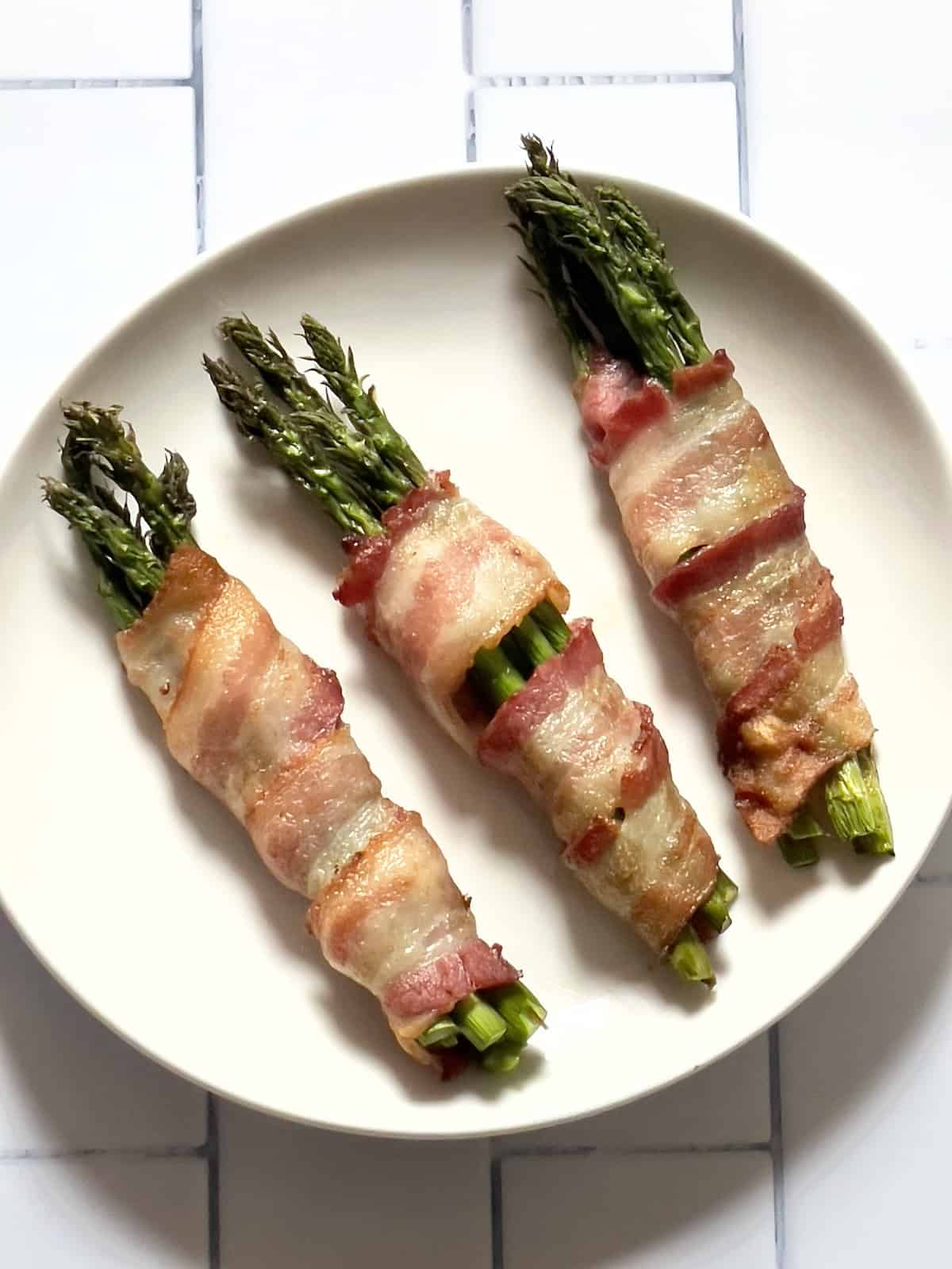 air fried bacon wrapped asparagus on a white plate on a white background