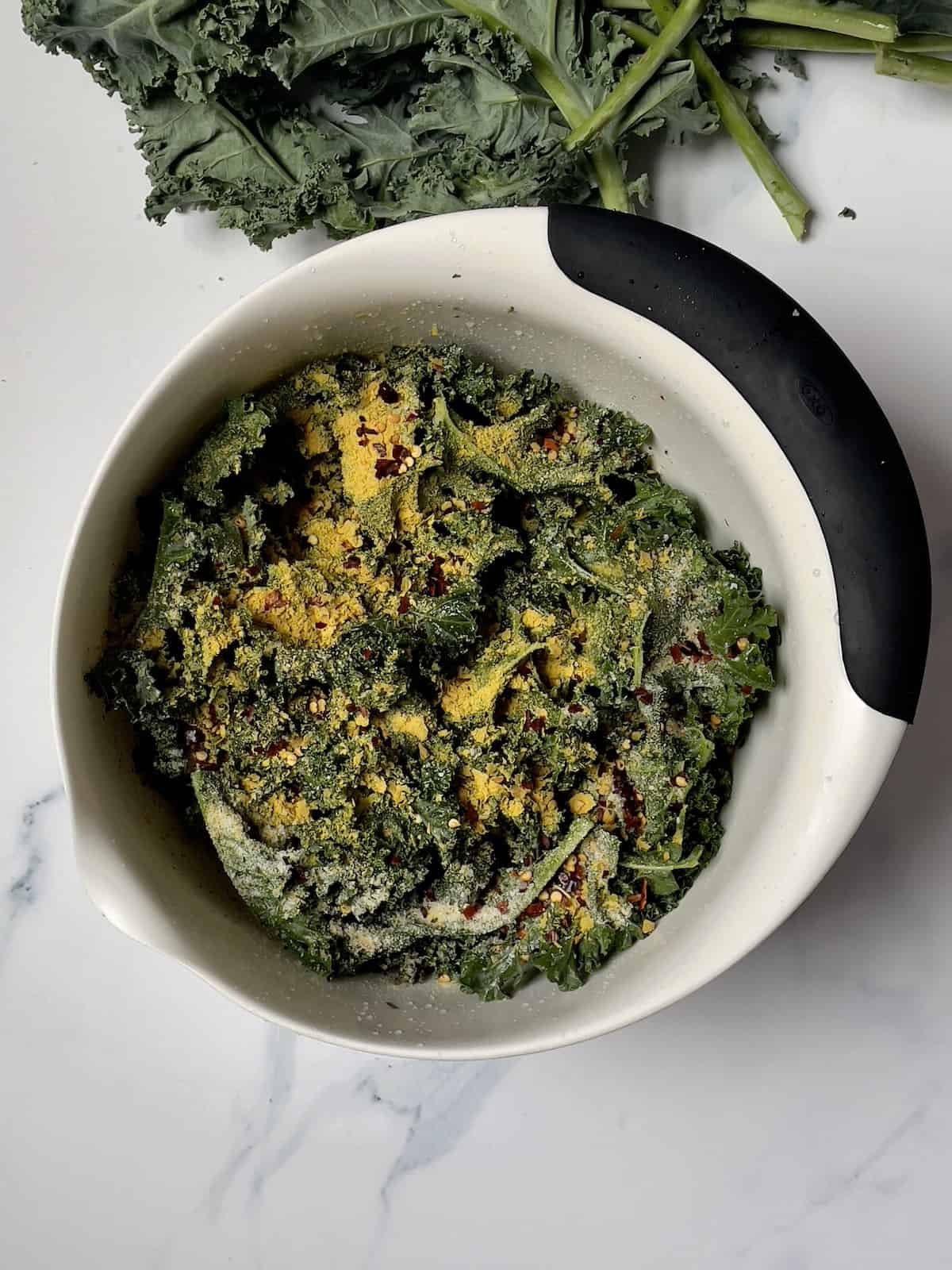 kale and seasonings in a white mixing bowl