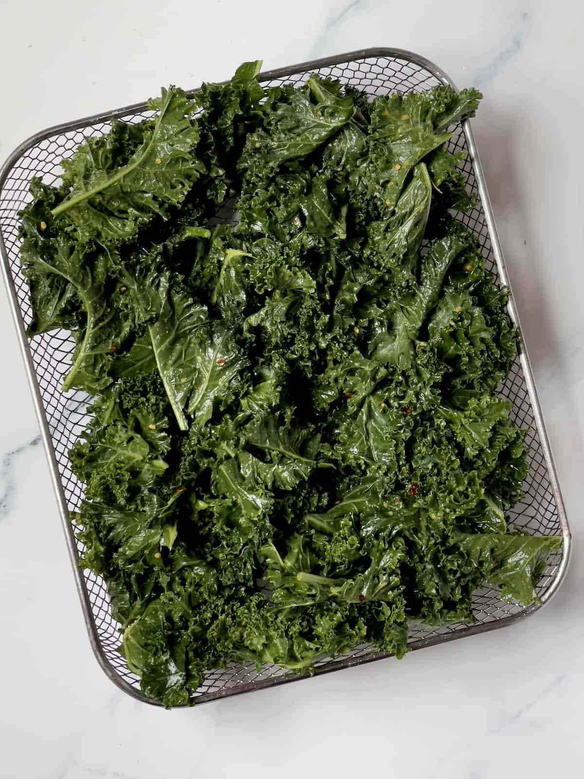 uncooked kale on an air fryer basket