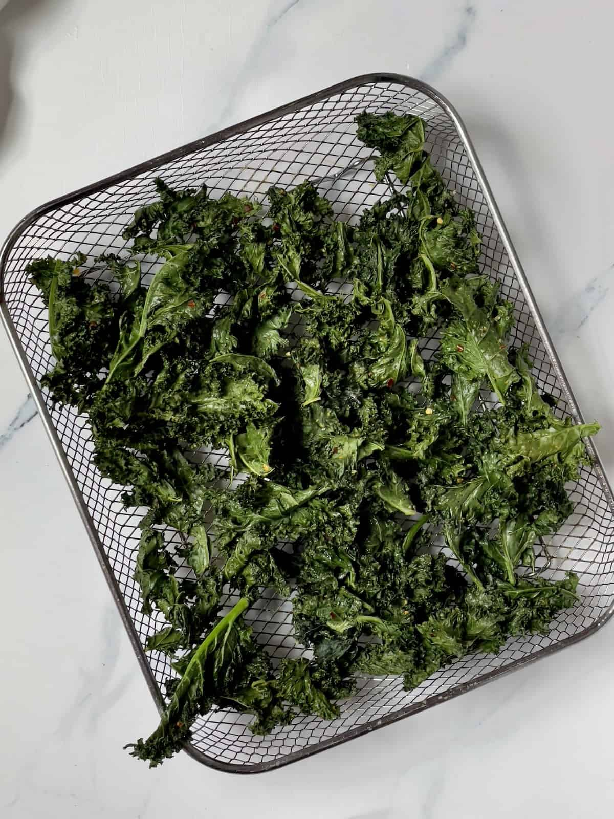 cooked kale chips in an air fryer basket