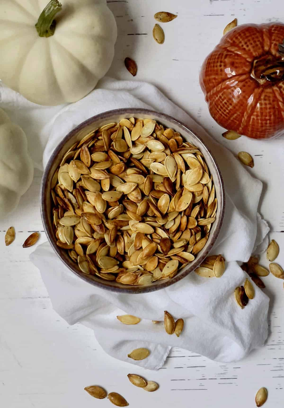 air fryer pumpkin seeds in a bowl surrounded by white pumpkins