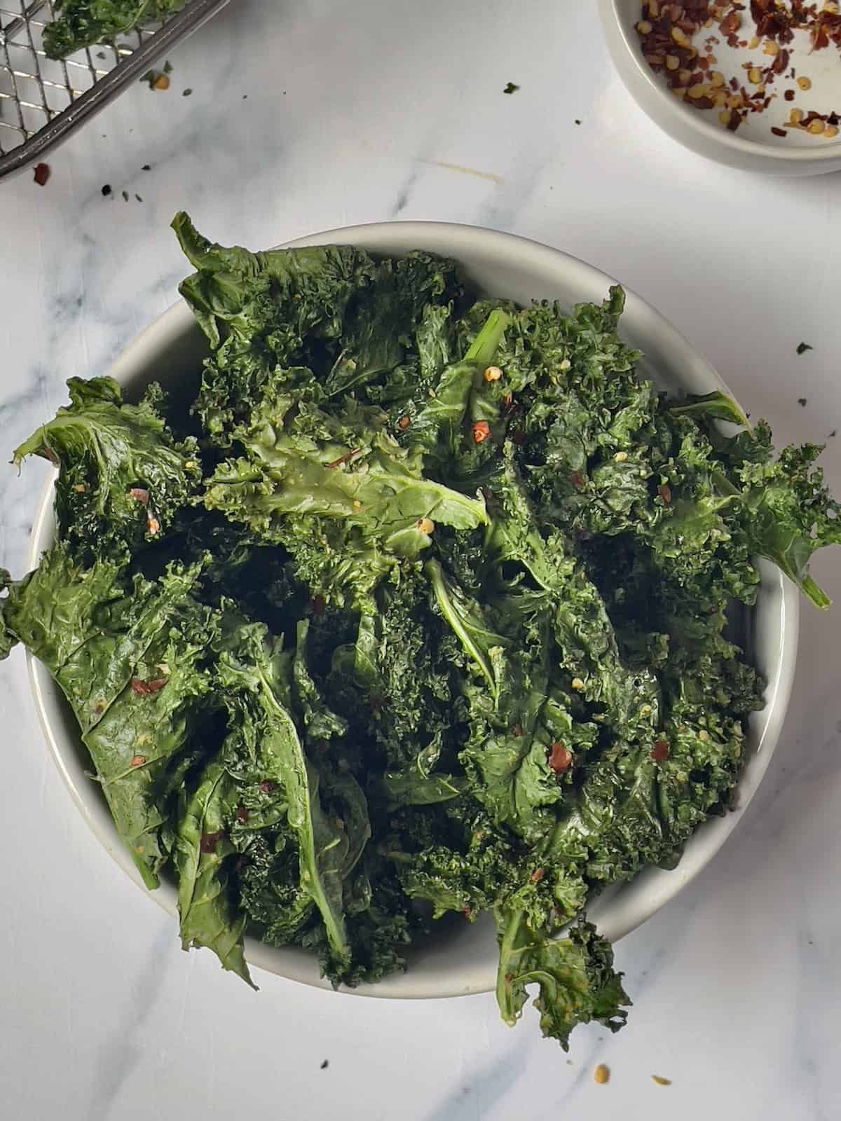 kale chips in a white bowl topped with red pepper flakes