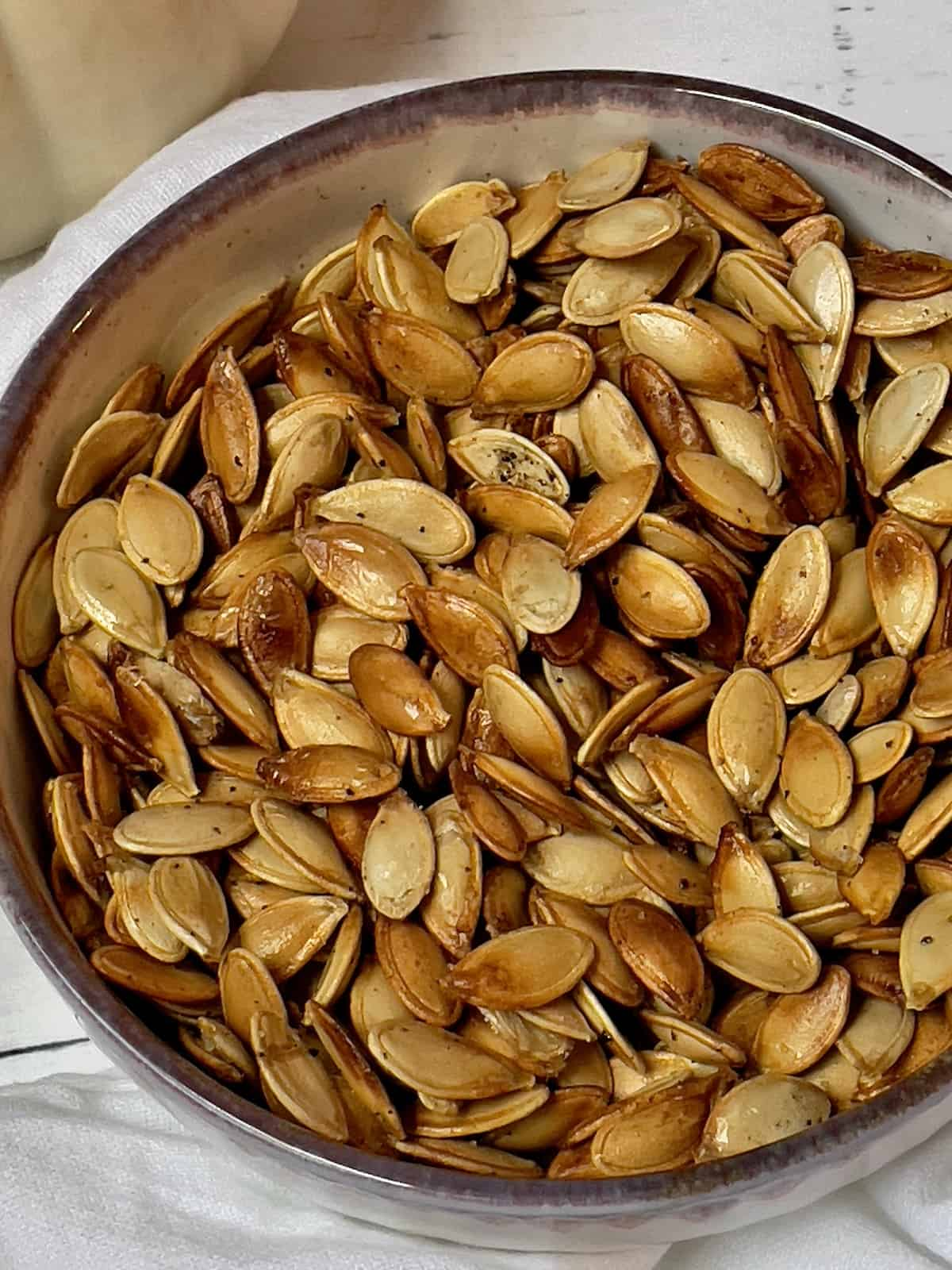 close up of roasted pumpkin seeds in a bowl