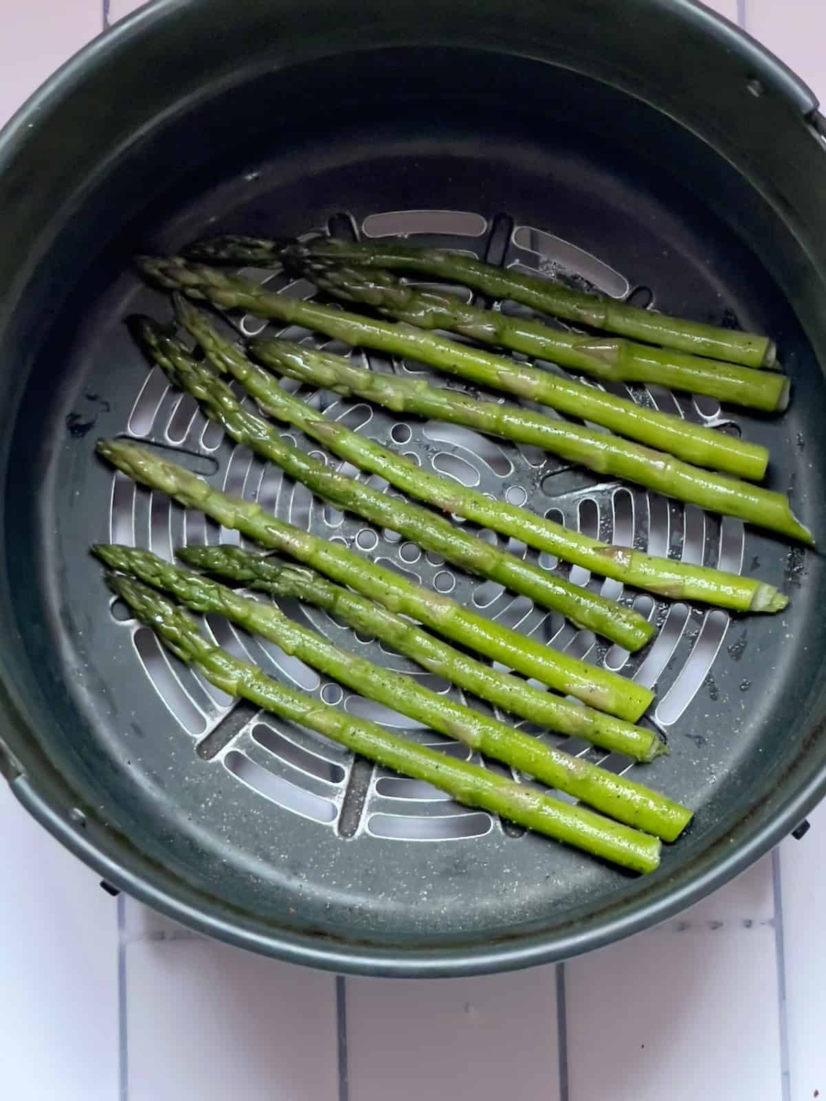 uncooked asparagus stalks in an air fryer basket