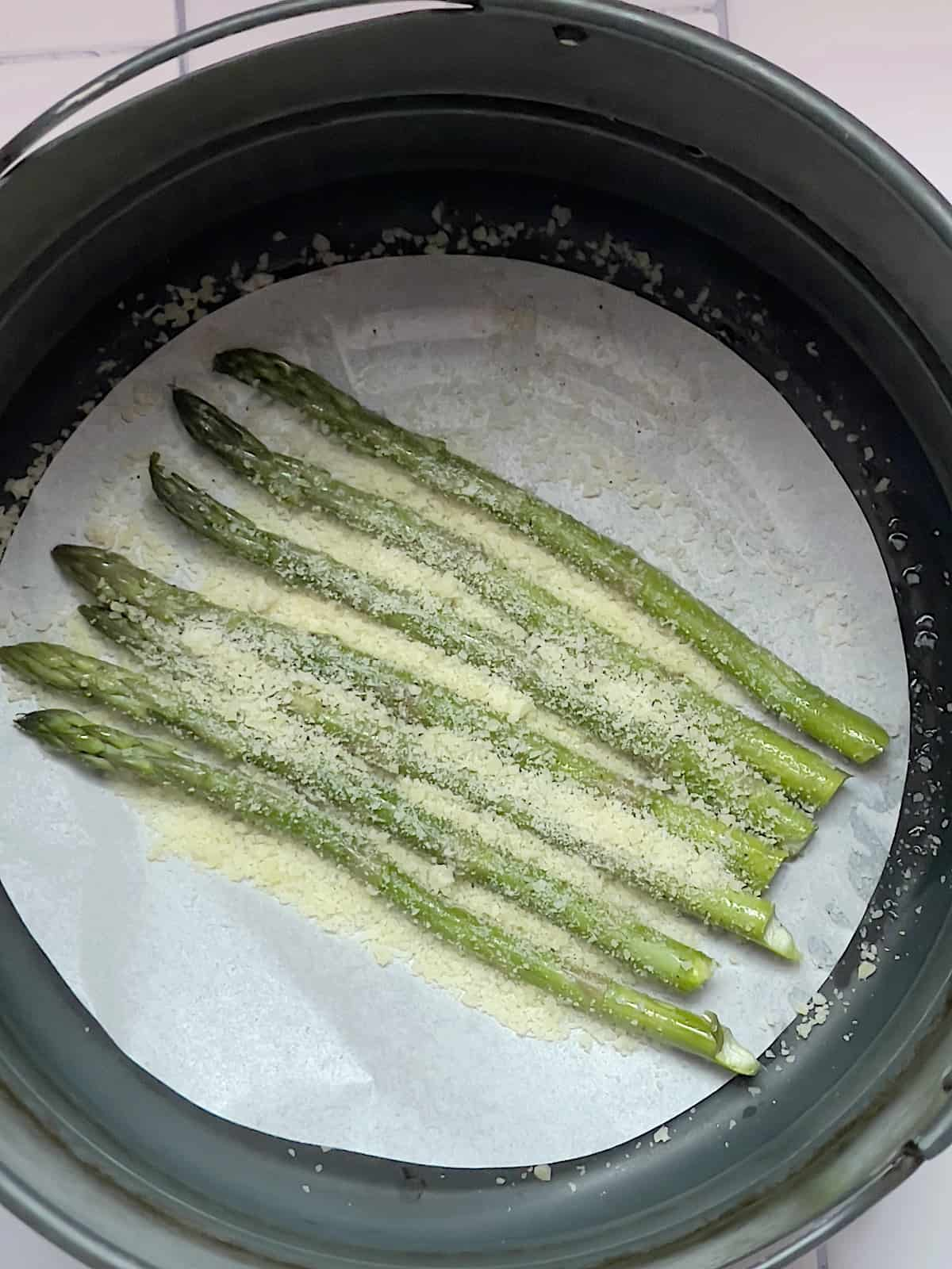 asparagus spears in an air fryer basket topped with parmesan cheese