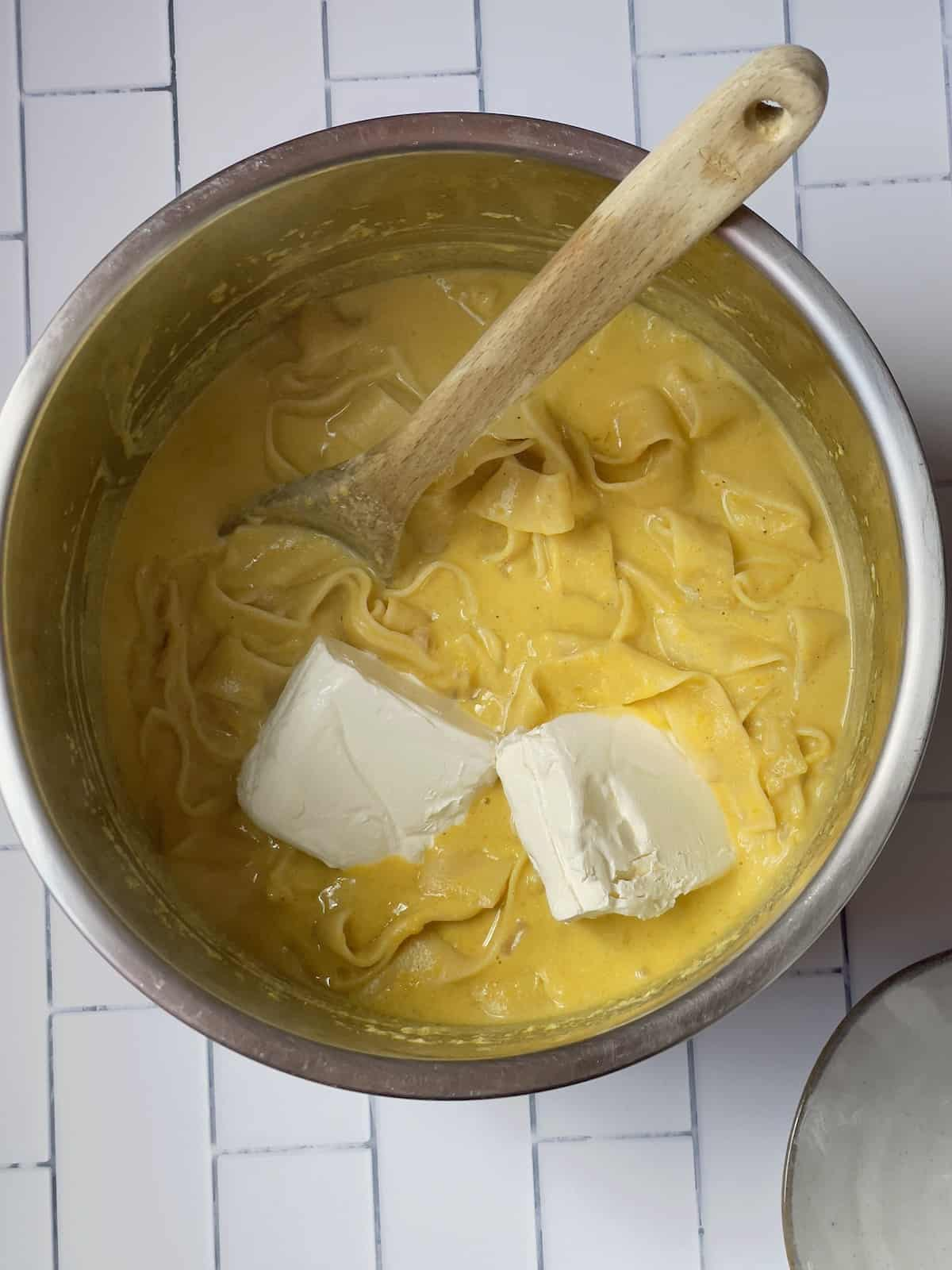 cream cheese being mixed into pumpkin pasta sauce in a pressure cooker
