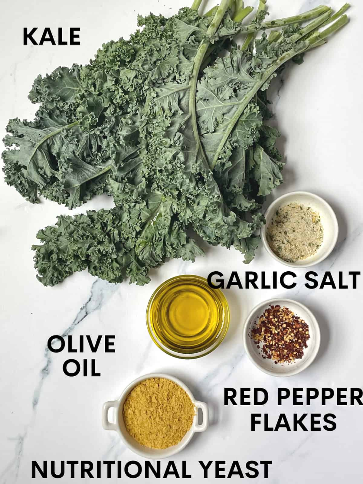 kale leaves, garlic salt, red pepper flakes, olive oil and nutritional yeast on a white cutting board
