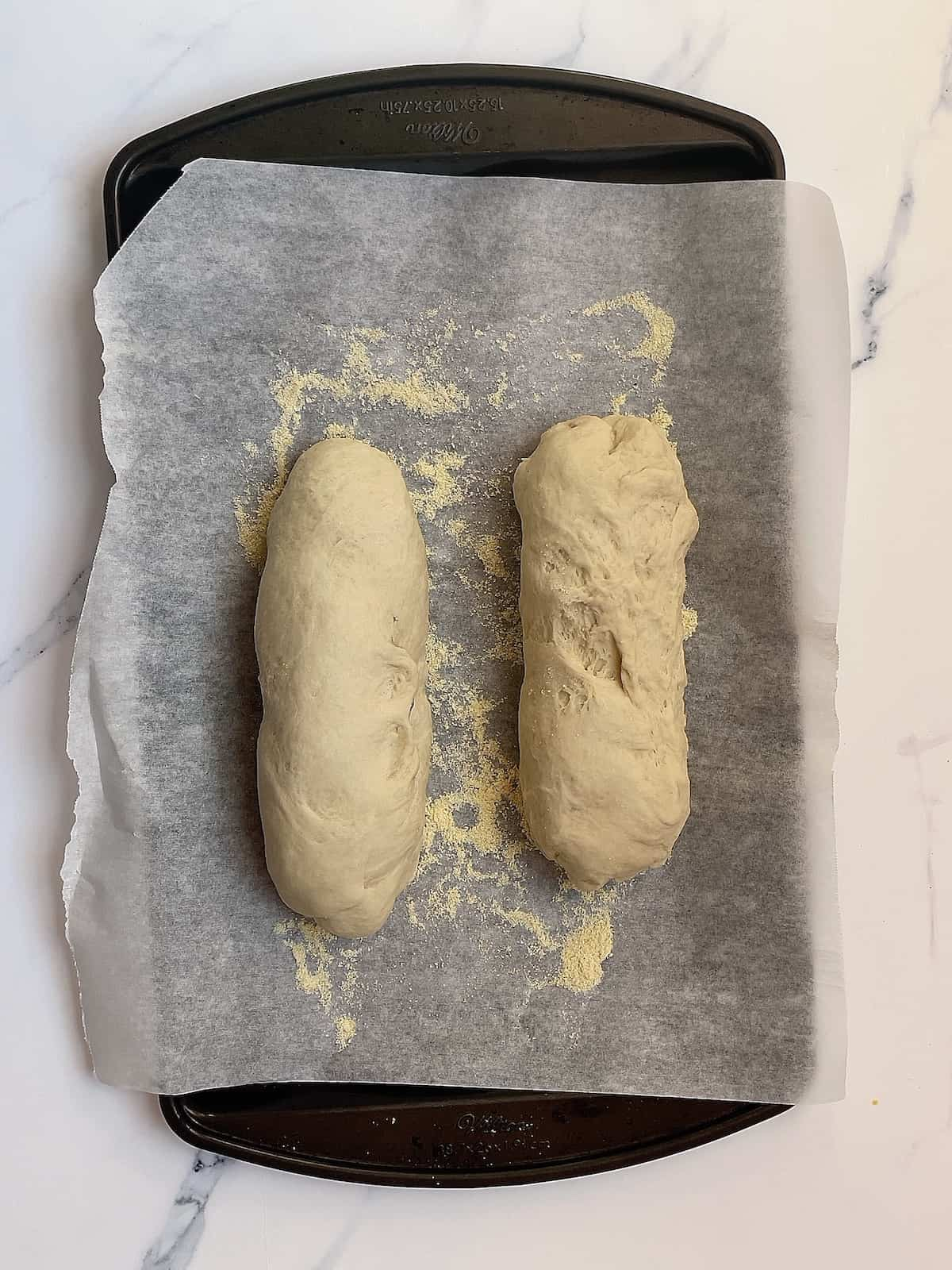 2 shaped loaves of bread on a baking sheet
