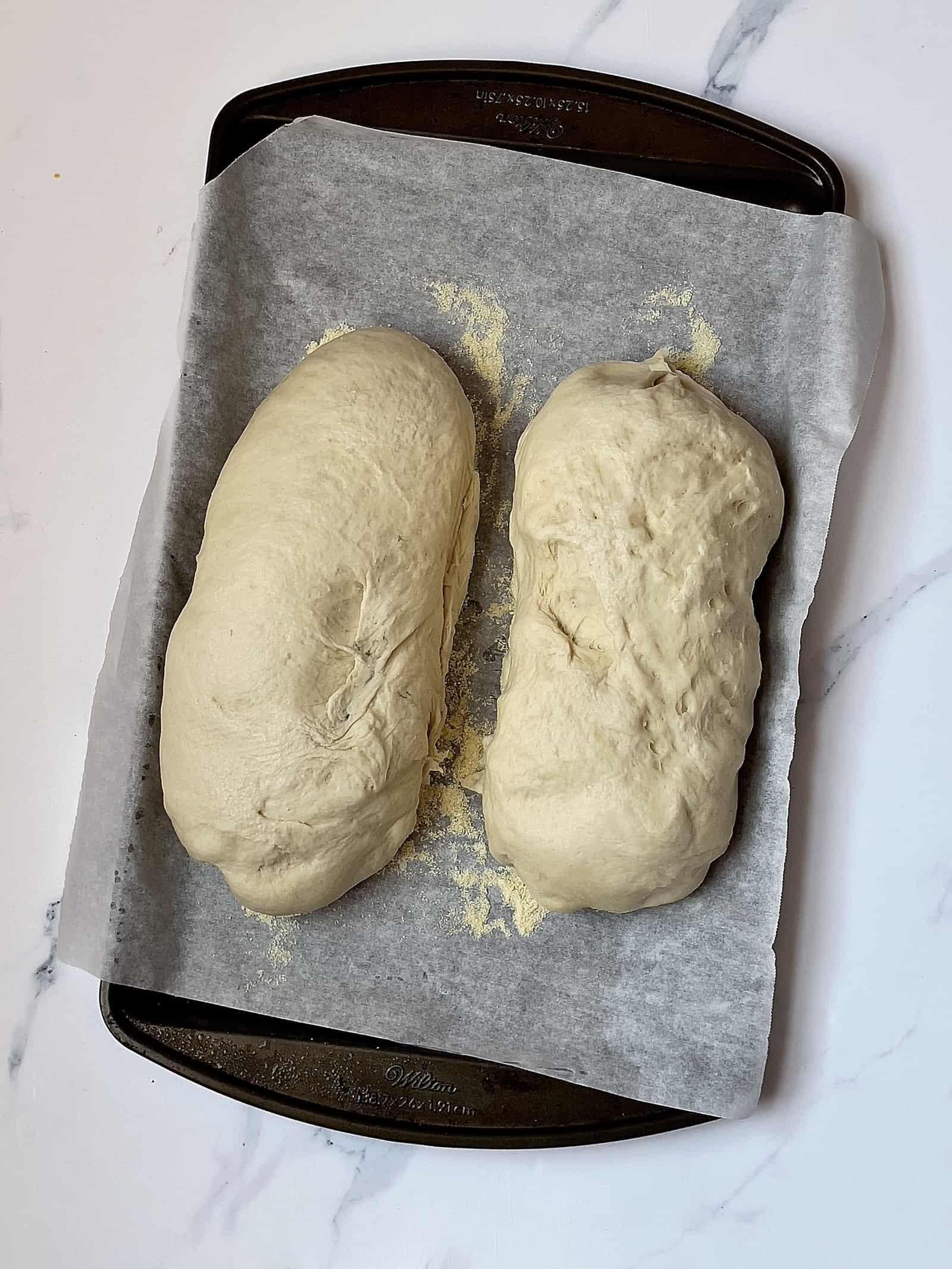2 risen loaves of dough on a baking sheet