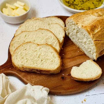 bread machine italian bread on a cutting board, sliced into pieces with butter and dipping oil