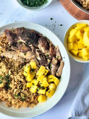instant pot jerk chicken and rice with mango and cilantro on a white plate
