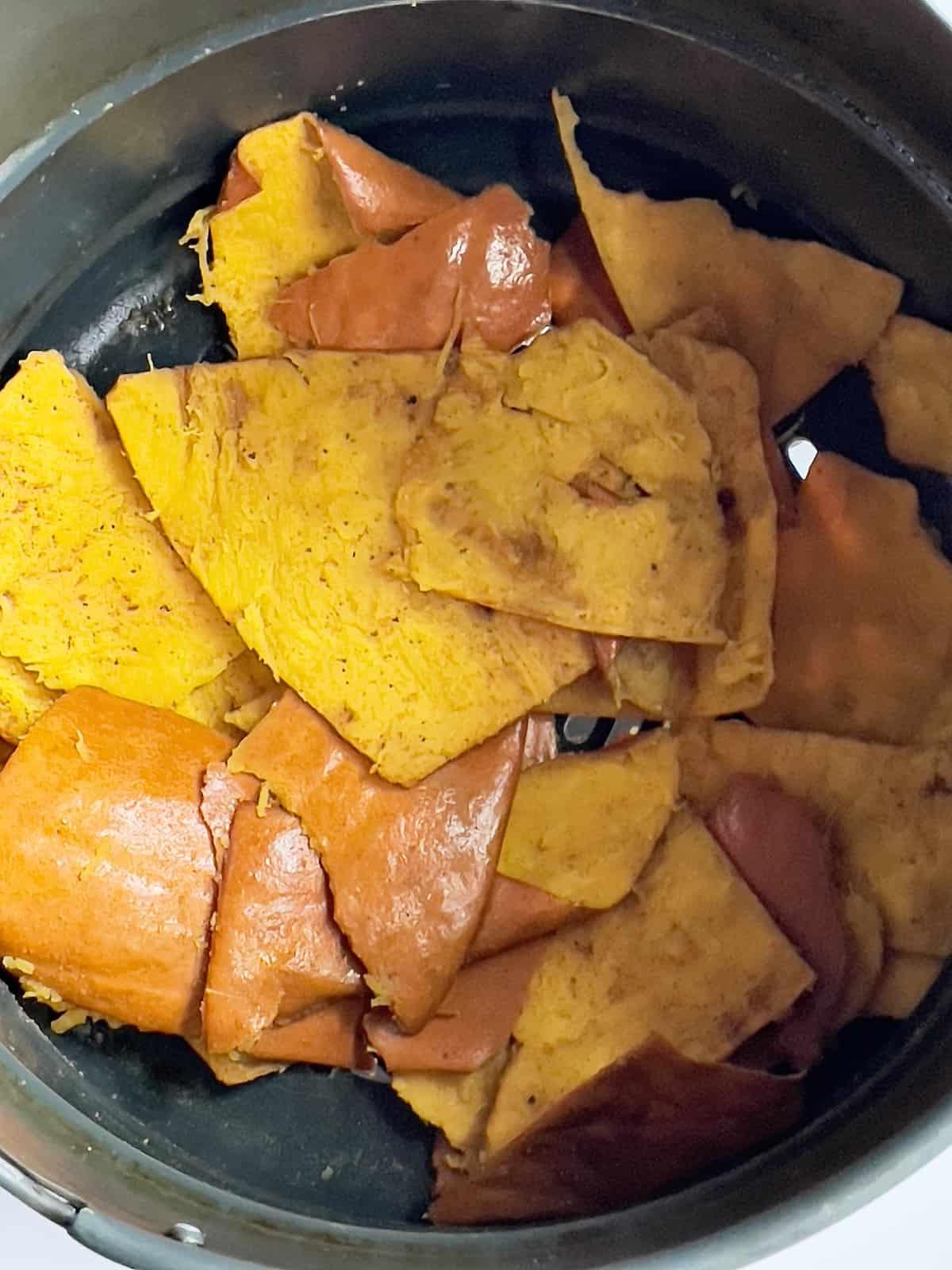 uncooked pumpkin skin tossed with seasonings in an air fryer basket